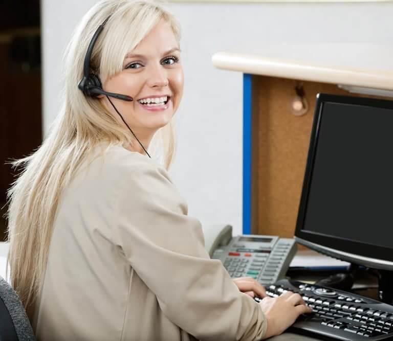 Blonde woman at computer smiling